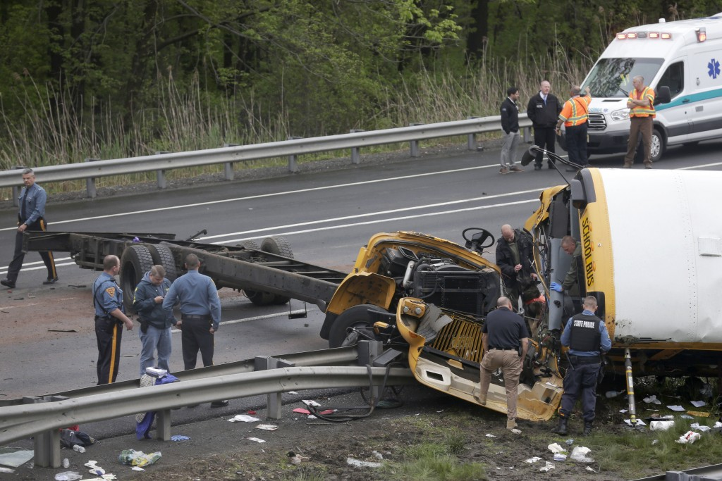 Emergency personnel examine a school bus after it collided with a dump truck, injuring multiple people, on Interstate 80 in Mount Olive, N.J., Thursda