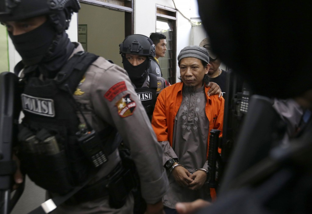 Islamic cleric Aman Abdurrahman, center, is escorted by police officers upon arrival for his trial at South Jakarta District Court in Jakarta, Indones
