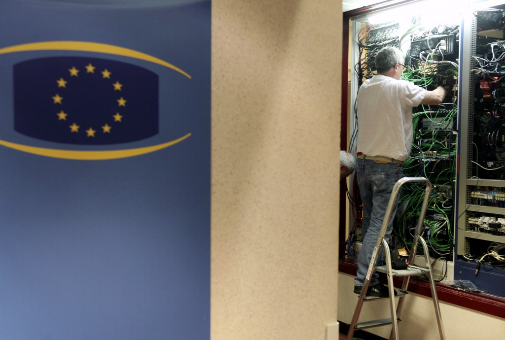 FILE- In this July 1, 2013, file photo, a communication technician works at a phone and internet cable closet, at the European Council building in Bru