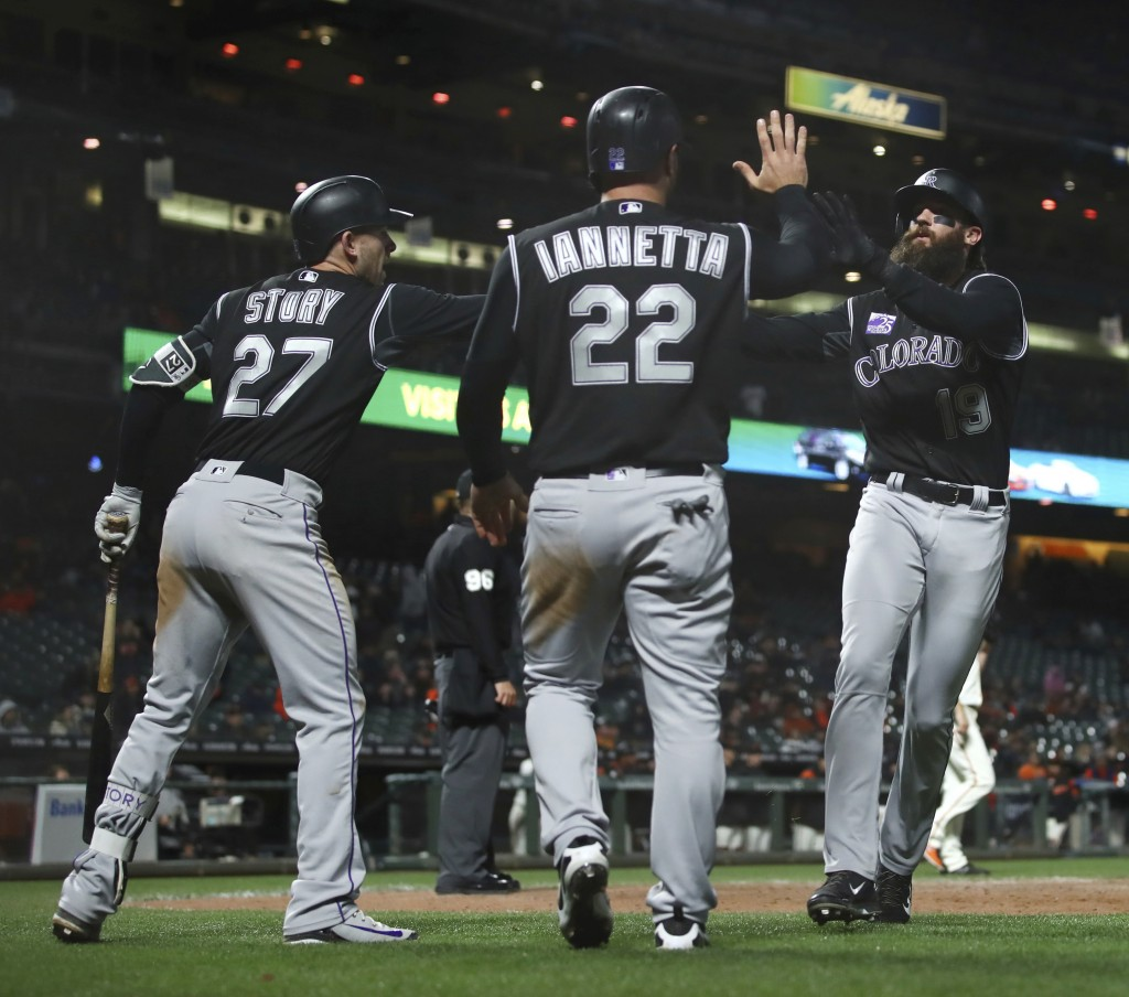 Colorado Rockies' Charlie Blackmon, right, celebrates with Trevor Story (27) and Chris Iannetta (22) after scoring against the San Francisco Giants in