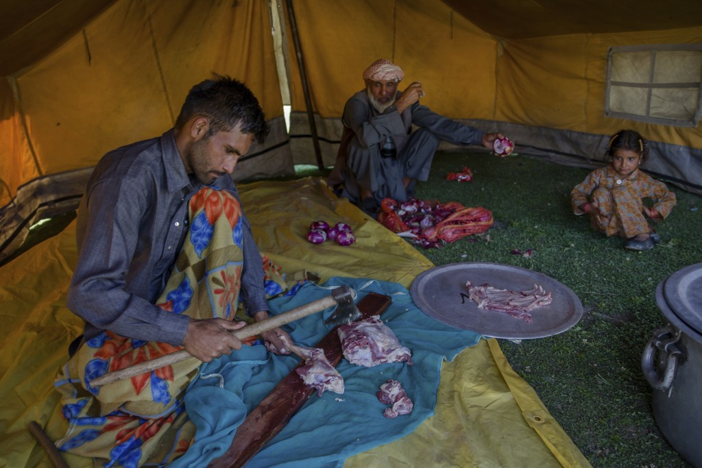 In this May 10, 2018, photo, Mohammad Aslam Khan, a Kashmiri nomadic Bakarwal cuts goat meat for a wedding feast at a camp in outskirts of Srinagar, I