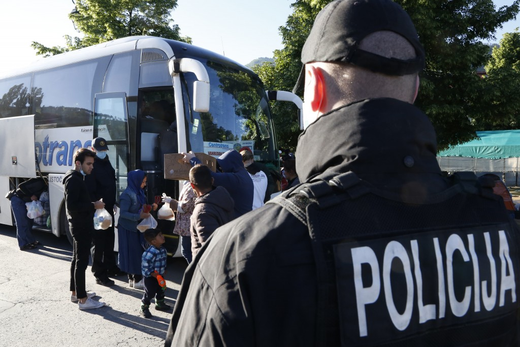A police officer stands guard by a bus with migrants on board during the evacuation of a makeshift camp in a park across from the City Hall, in Saraje