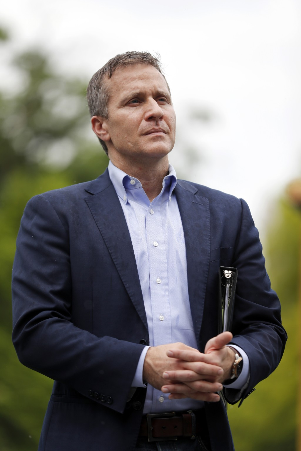Missouri Gov. Eric Greitens stands off to the side before stepping up to the podium to deliver remarks to a small group of supporters near the capitol