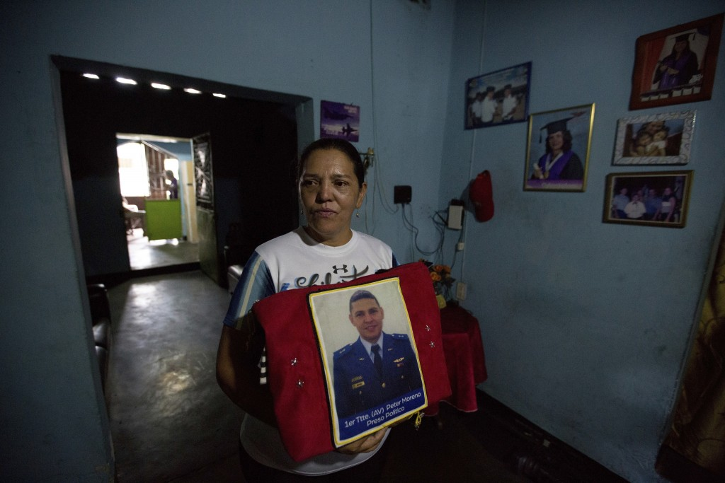 In this Feb. 22, 2018 photo, Marilu Moreno holds a picture of her son Peter Moreno, an Air Force Lieutenant who was arrested for alleged conspiracy ag