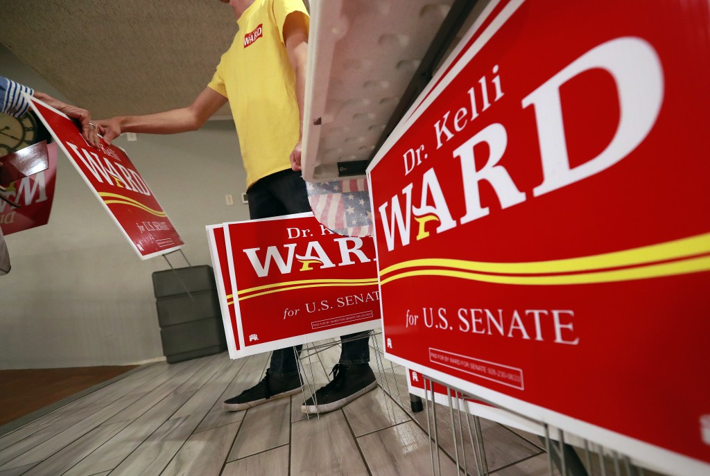 In this Tuesday, May 8, 2018 photo, a volunteer hands out U.S. Senatorial candidate Kelli Ward campaign signs to volunteers and voters during the Sun