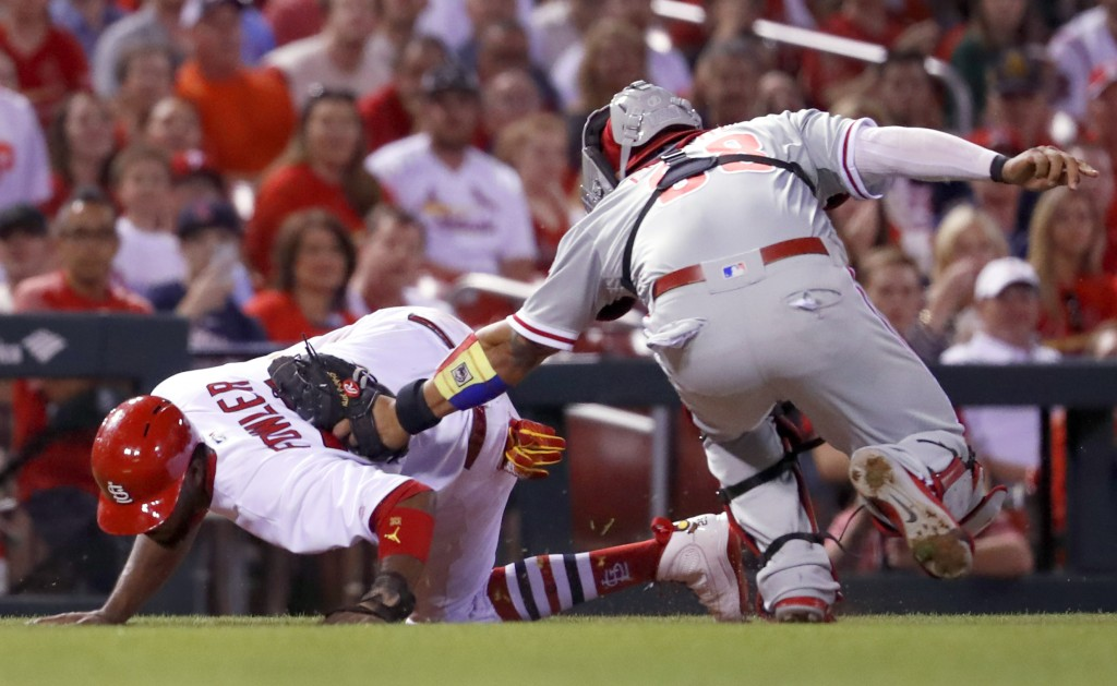 St. Louis Cardinals' Dexter Fowler, left, is tagged out by Philadelphia Phillies catcher Jorge Alfaro after being caught between third and home during