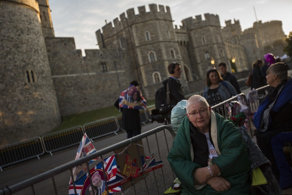 A woman sits after spending the night in front of Windsor castle, England, Friday, May 18, 2018. Preparations continue in Windsor ahead of the royal w