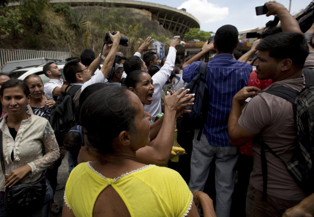 The relatives of prisoners shout slogans against presidential candidate Javier Bertucci outside the Political Police headquarters and jail in Caracas,