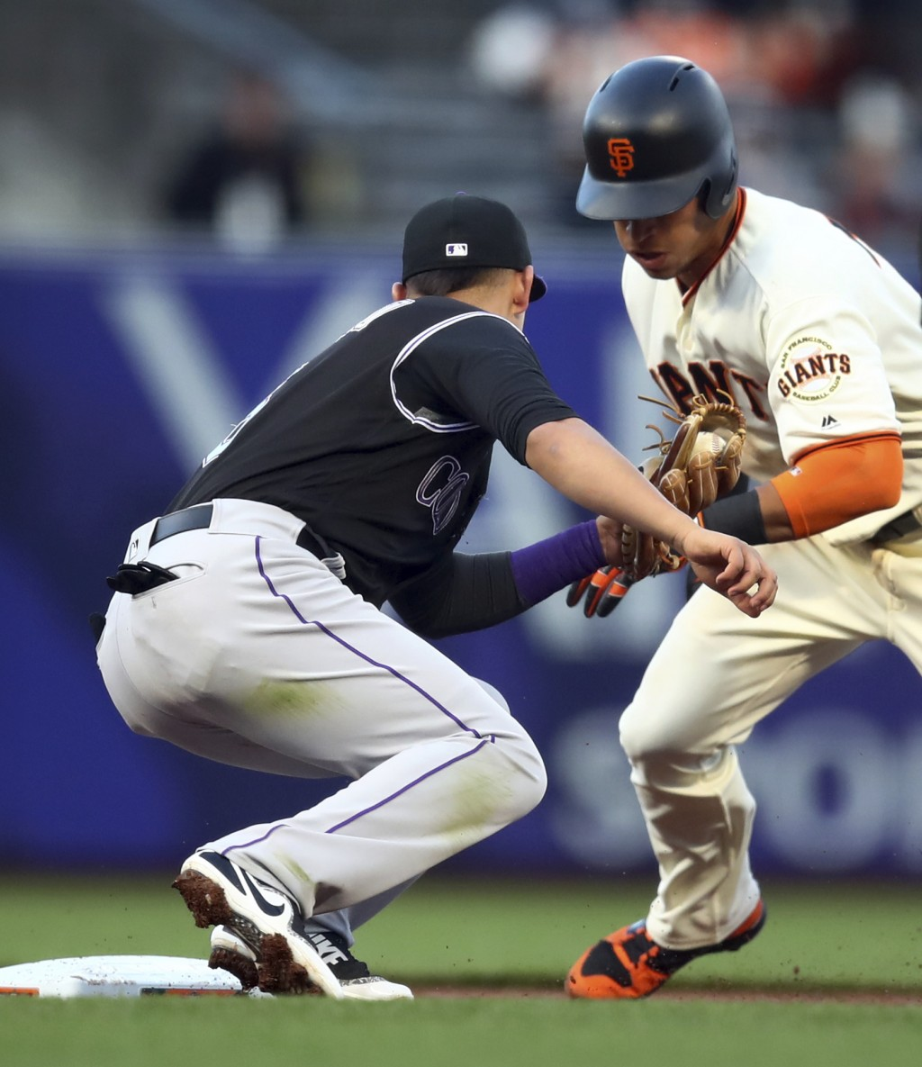 Colorado Rockies' Daniel Castro, left, tags out San Francisco Giants' Gorkys Hernandez on a first-inning attempted steal of second base during a baseb
