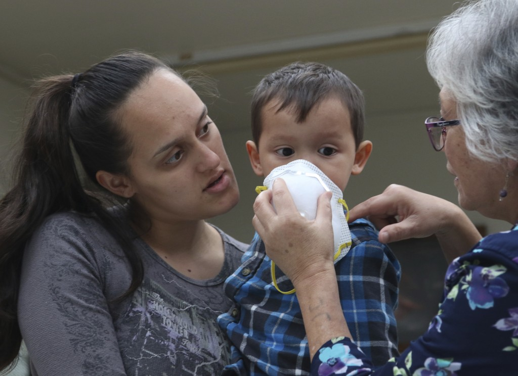 Lindsey Magnani and her son Kahele Rodrigues, 2, listen as an official shows them how to use a respirator that was given to them to help protect again