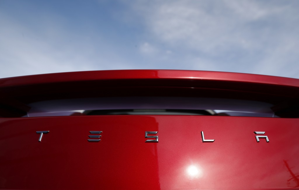 FILE- In this April 15, 2018, photo, the sun shines off the rear deck of a roadster on a Tesla dealer's lot in the south Denver suburb of Littleton, C