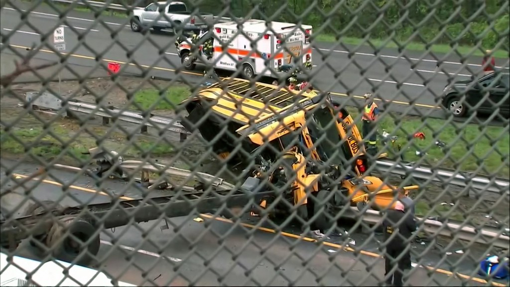 This image taken from WABC-TV video shows an overturned school bus after it collided with a dump truck, injuring multiple people, on Interstate 80 in