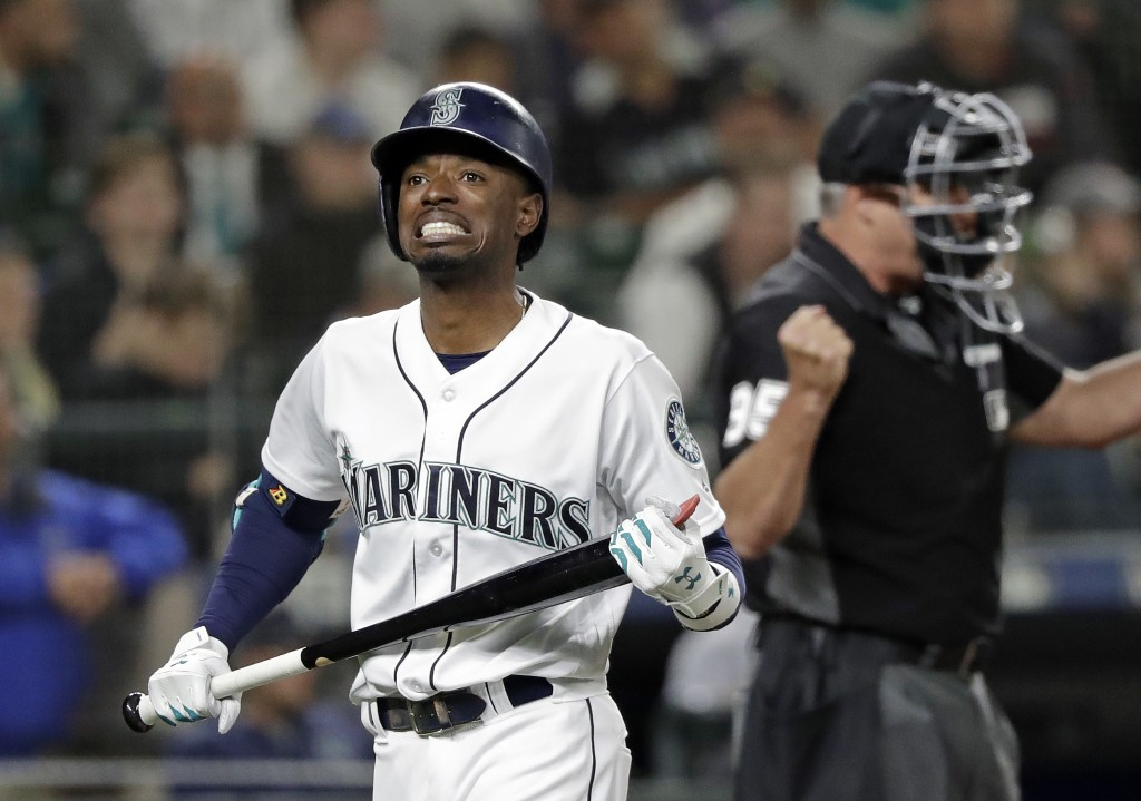 Seattle Mariners' Dee Gordon heads back to the dugout after striking out swinging as umpire Tim Timmons signals the out during the seventh inning of t