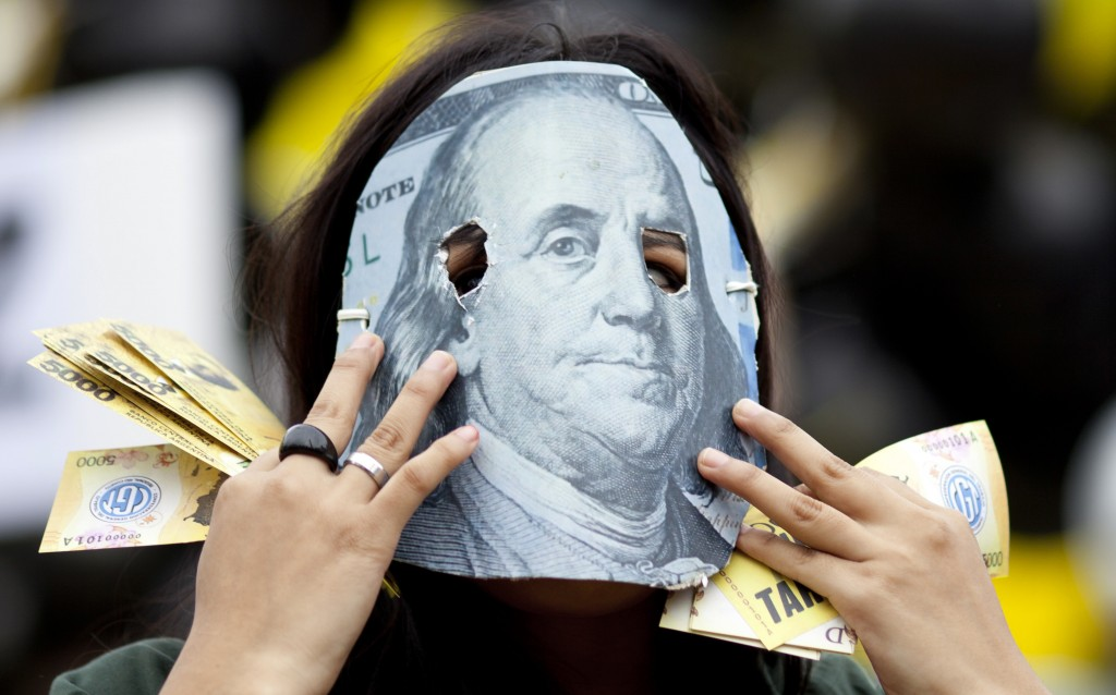 In this Monday, May 14, 2018 photo, a demonstrator wears an oversized 100 U.S. dollar bill as a mask to protest the government's plan to make a deal w
