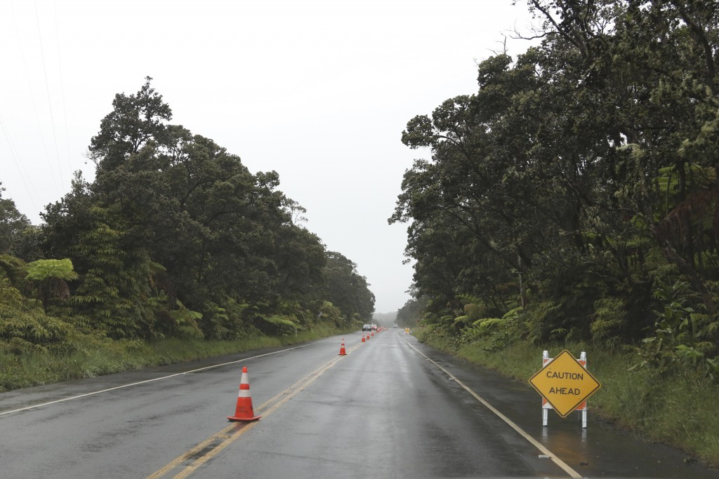 Cones and signs warn of cracks in the road near the entrance to Hawaii Volcanoes National Park, Thursday, May 17, 2018, near Volcano, Hawaii. (AP Phot