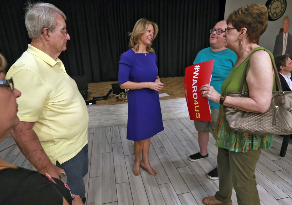 In this Tuesday, May 8, 2018 photo, U.S. Senatorial candidate Kelli Ward, center, speaks to volunteers and voters after the Sun Lakes Republican Club