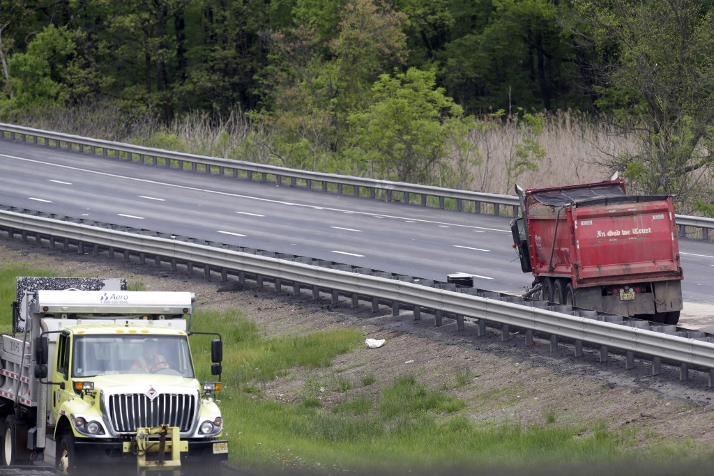A dump truck sits on the road after it collided with a school bus, injuring multiple people, on Interstate 80 in Mount Olive, N.J., Thursday, May 17,