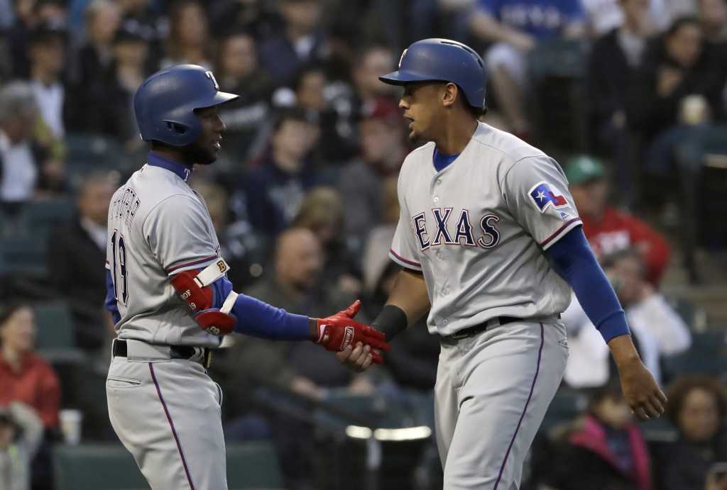 Texas Rangers' Ronald Guzman, right, celebrates with Jurickson Profar after scoring on a single by Shin-Soo Choo during the third inning of a baseball