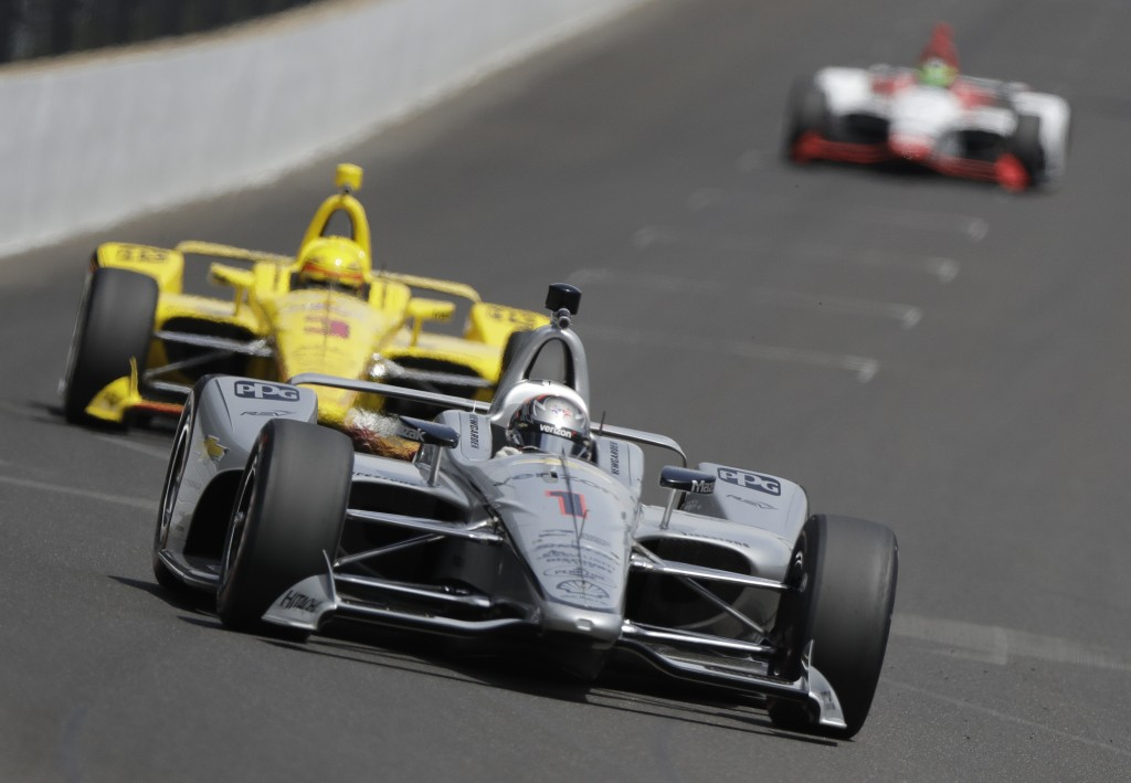 Josef Newgarden leads Helio Castroneves, of Brazil, into turn one during a practice session for the IndyCar Indianapolis 500 auto race at Indianapolis