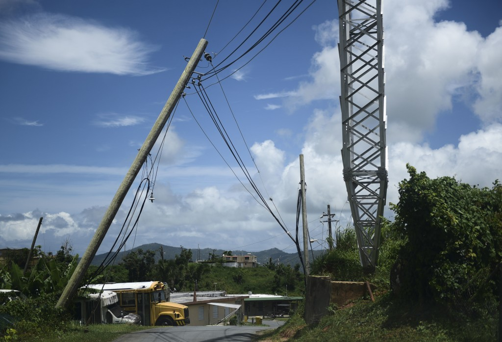 In this May 16, 2018 photo, an electric power pole leans over the road in the Piedra Blanca area of Yabucoa, Puerto Rico. Most of those still without