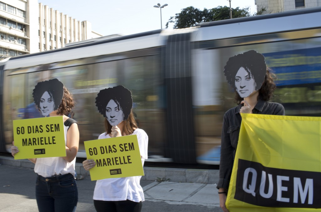 "In this Monday, May 14, 2018 photo, women wearing masks of slain councilwoman Marielle Franco hold signs that say in Portuguese: ""60 days without Mari"