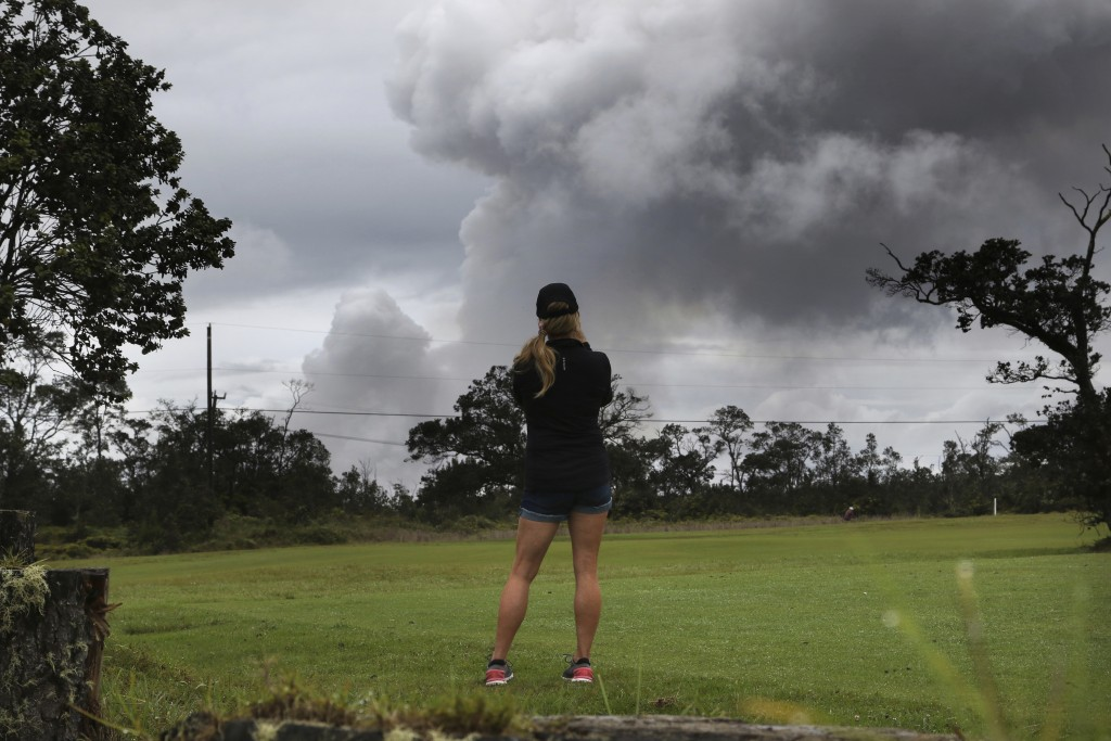 Marie Brant, of Laguna Niguel, Calif., watches as ash rises from the summit crater of Kilauea volcano, Thursday, May 17, 2018, in Volcano, Hawaii. Bra