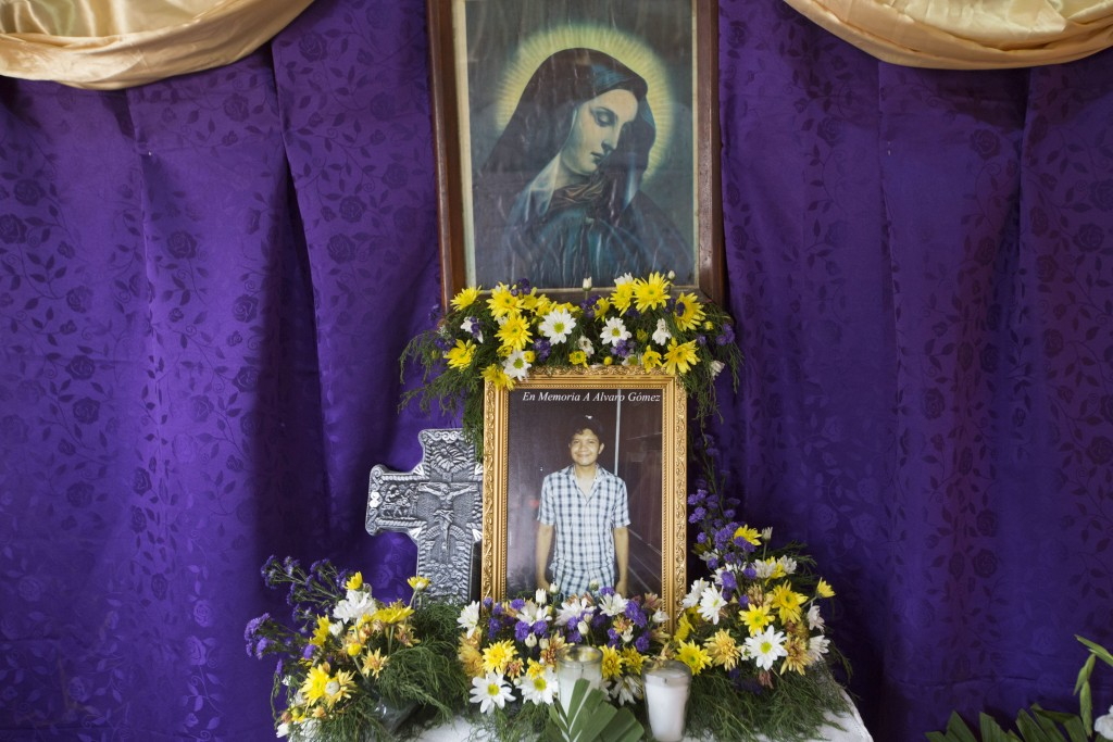 In this May 2, 2018 photo, an altar dedicated to 23-year-old Alvaro Gomez is adorned with an image of Nicaragua's patron saint La Purisima and a cruci