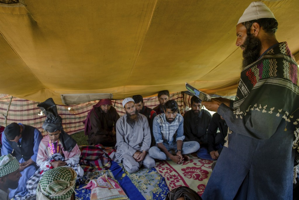 In this May 11, 2018, photo, Kashmiri Bakarwal nomads listen to a sermon delivered by a cleric during a marriage ceremony at a camp in the outskirts o