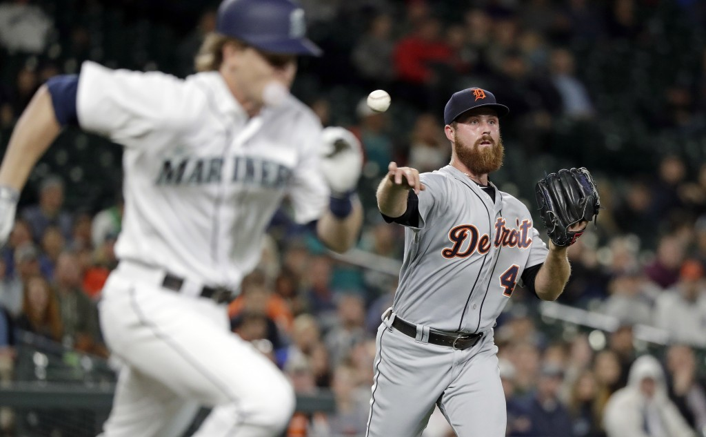 Detroit Tigers relief pitcher Buck Farmer throws to first as Seattle Mariners' Gordon Beckham races to the bag on a sacrifice bunt during the seventh