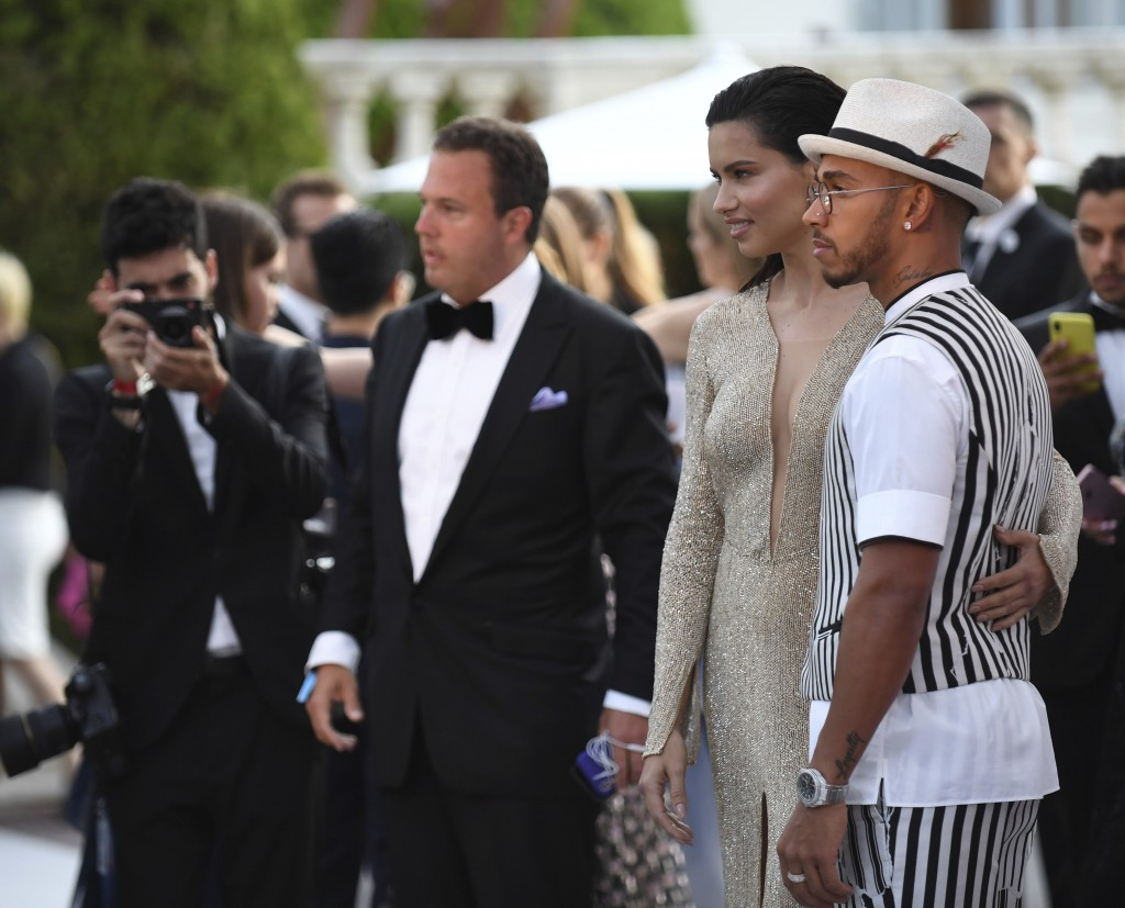 Formula 1 racing driver Lewis Hamilton, right, and model Adriana Lima pose for photographers upon arrival at the amfAR, Cinema Against AIDS, benefit a
