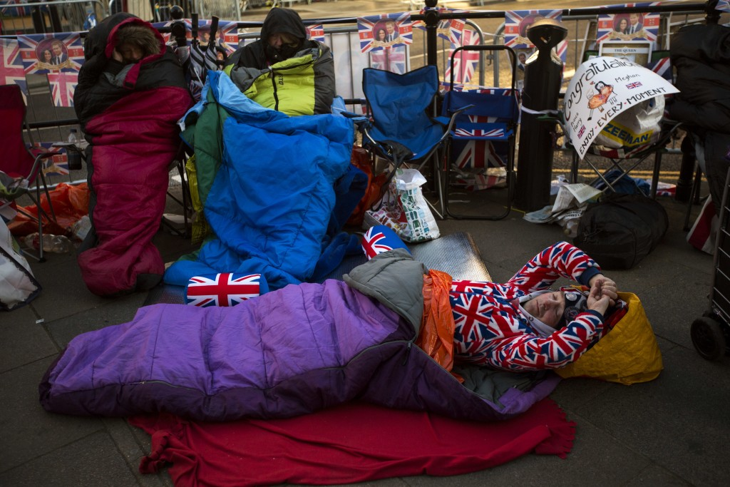 A man sleeps on the ground, spending the night near Windsor castle, England, Friday, May 18, 2018. Preparations continue in Windsor ahead of the royal