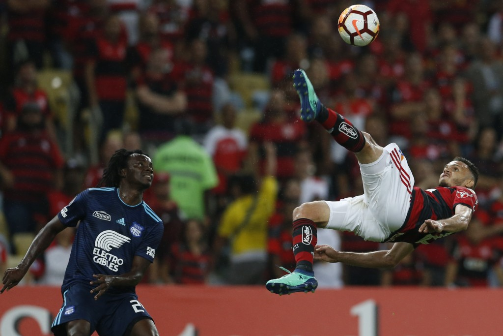 In this Wednesday, May 16, 2018 photo, Rene of Brazil's Flamengo, right, executes a bicycle kick next to Juan Carlos Paredes of Ecuador's Emelec at a