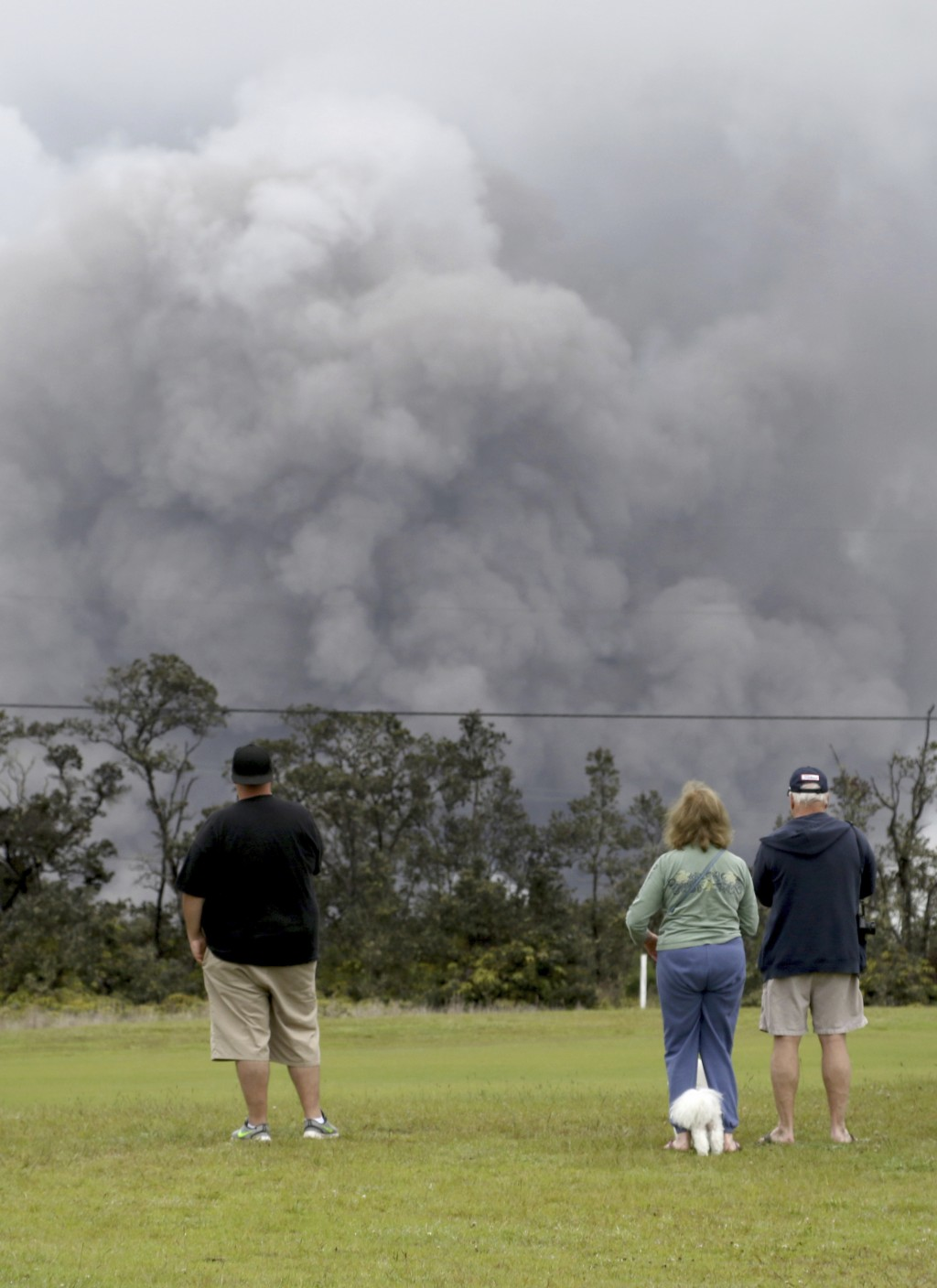 People watch as ash rises from the summit crater of Kilauea volcano, Thursday, May 17, 2018, in Volcano, Hawaii. The volcano on Hawaii's Big Island er