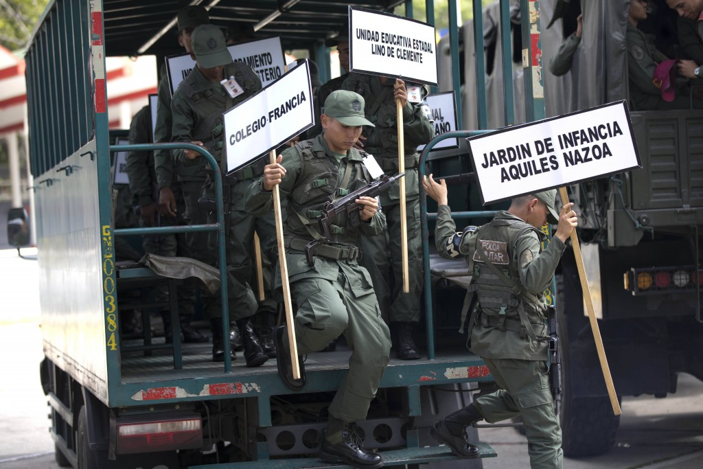 In this Tuesday, May 15, 2018 photo, soldiers carrying signs with the names of schools that will serve as voting centers, exit a military truck as the