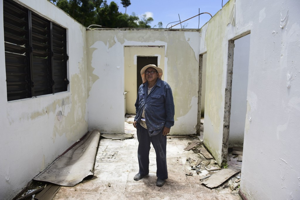 In this May 16, 2018 photo, tinsmith Otoniel Ramos Aponte poses for a portrait inside his mother's home, which lost its roof to Hurricane Maria but di