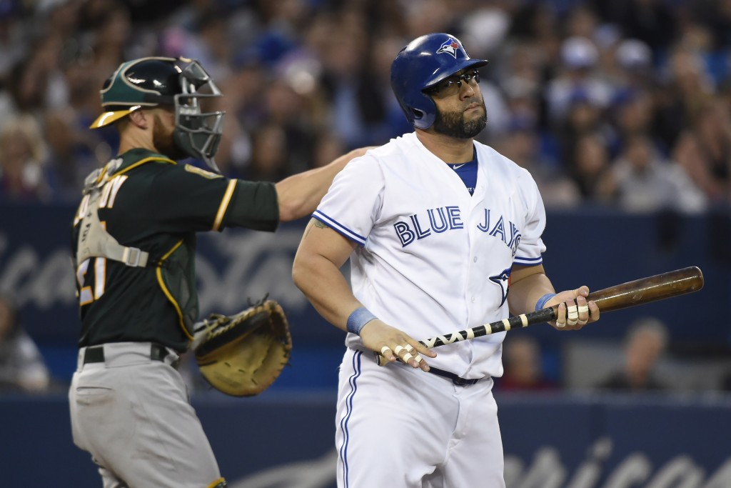 Toronto Blue Jays Jays' Kendrys Morales, right, reacts after taking a strike during the fourth inning of a baseball game against the Oakland Athletics