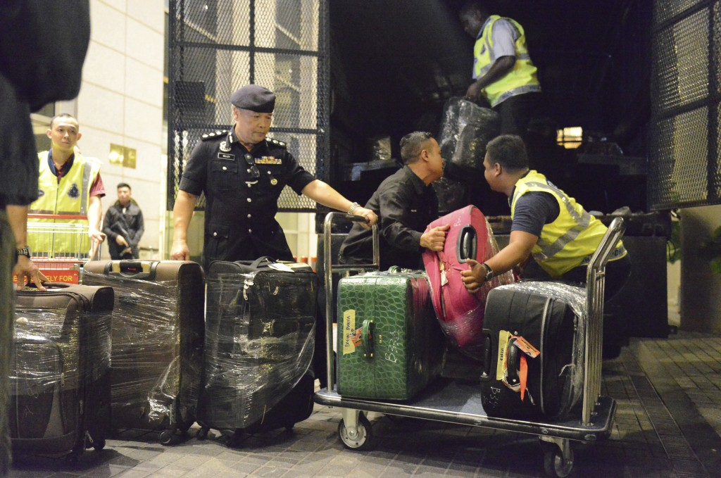 Police load confiscated items into a truck in Kuala Lumpur, Malaysia Friday, May 18, 2018. Malaysian police confiscated a few hundred designer handbag