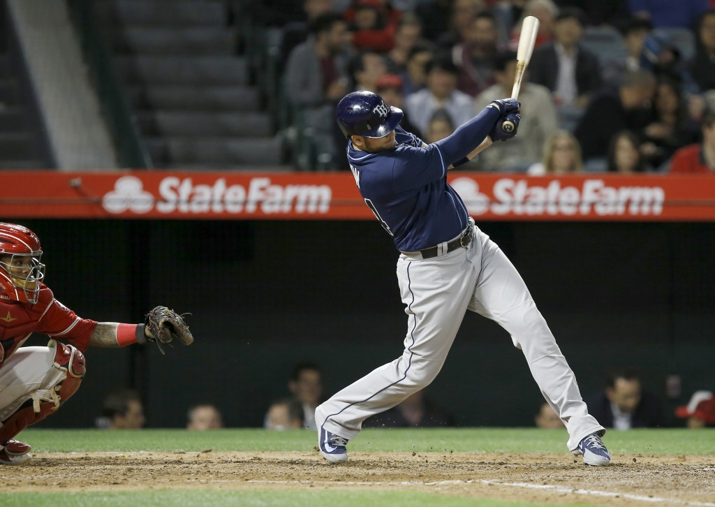 Tampa Bay Rays' C.J. Cron, right, hits a solo home run in front of Los Angeles Angels catcher Martin Maldonado during the sixth inning of a baseball g