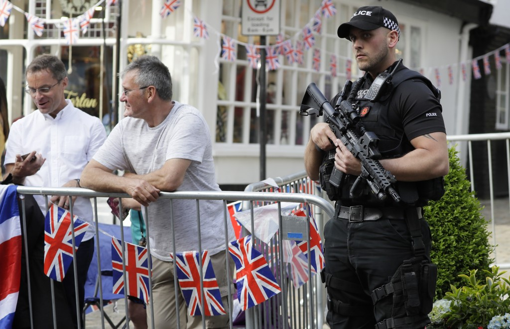 An armed police officer keeps guard as Prince William and Prince Harry greet the crowd waiting outside the castle in Windsor, England, Friday, May 18,...