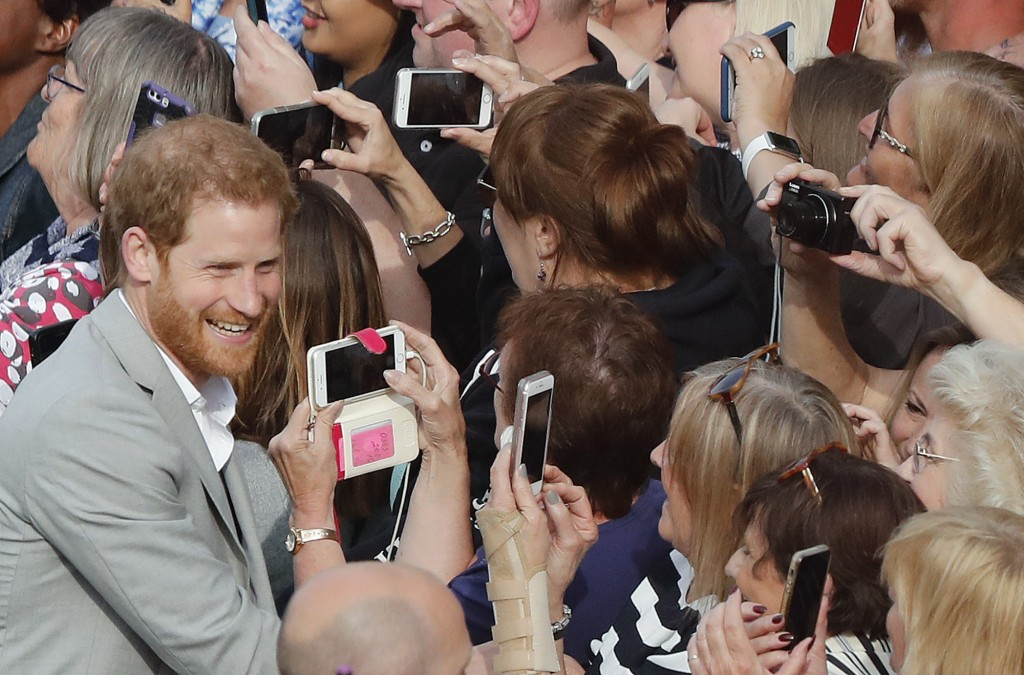 Britain's Prince Harry reacts as he greets crowds in Windsor, near London, England, Friday, May 18, 2018. Preparations continue in Windsor ahead of th...