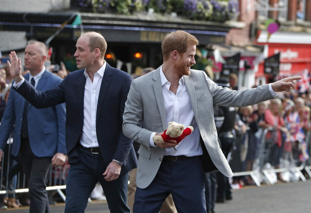 Britain's Prince Harry walks back carrying a cuddly toy after he greeted crowds with his brother Prince William in Windsor, near London, England, Frid...