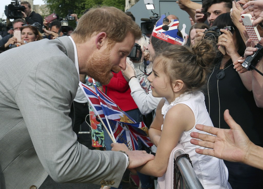 Britain's Prince Harry, left, greets a young well-wisher during a walkabout with Prince William outside Windsor castle, in Windsor, England, Friday, M...