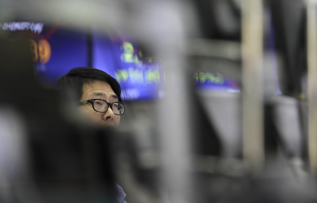 A currency trader watches computer monitors near the screen showing the Korea Composite Stock Price Index (KOSPI) at the foreign exchange dealing room...