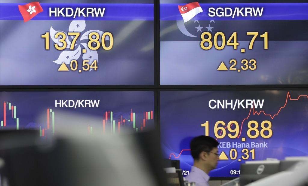 A currency trader walks by the screens showing the foreign exchange rates at the foreign exchange dealing room in Seoul, South Korea, Monday, May 21, ...