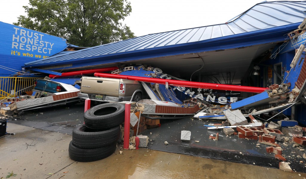 FILE- In this June 22, 2017, file photo, several cars sit under the collapsed roof of an Express Oil Change after a possible tornado touched down dest...