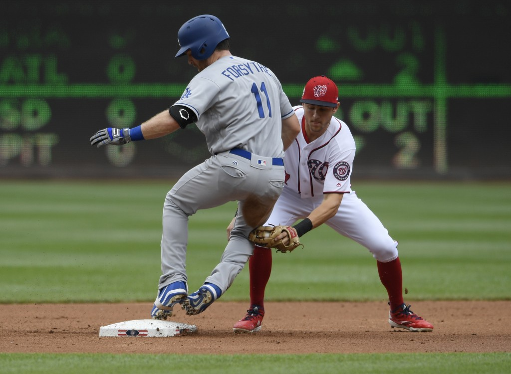 Los Angeles Dodgers' Logan Forsythe, left, is safe at second with a double against Washington Nationals shortstop Trea Turner, right, during the secon...