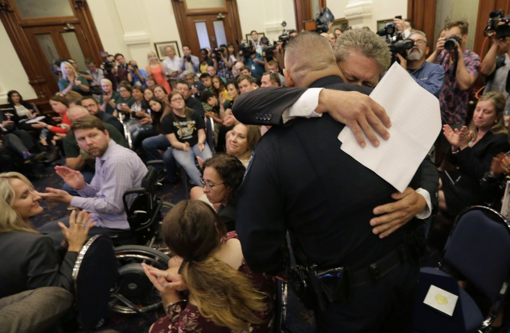 Scot Rice hugs Santa Fe Independent School District police officer John Banda after telling his story during a roundtable discussion in Austin, Texas,...