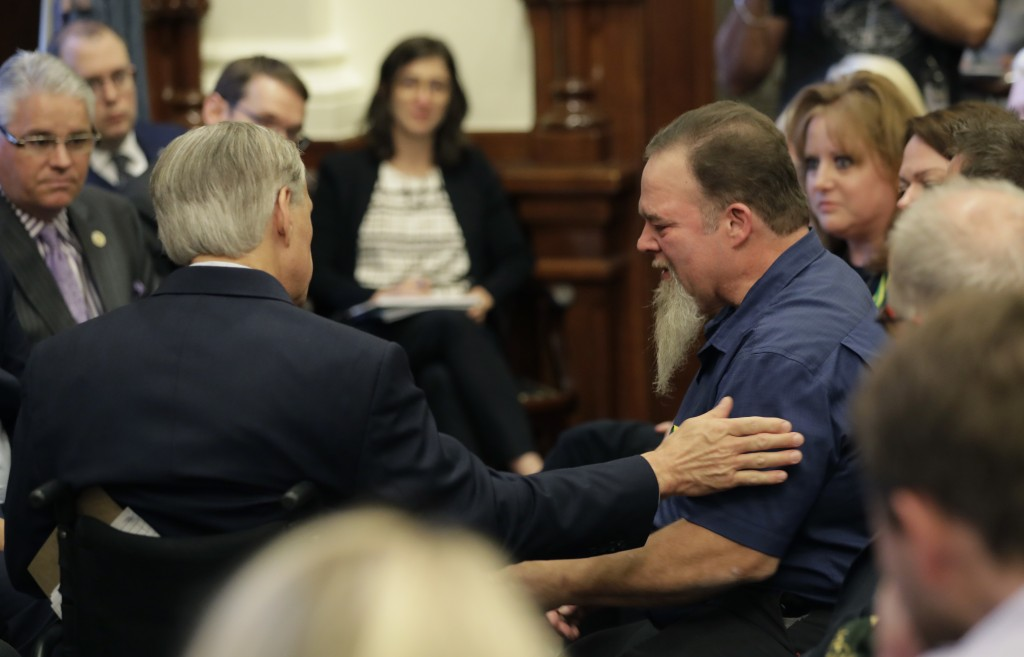 Texas Gov. Gregg Abbott, left, reached out to a man holding back tear as he speaks during a roundtable discussion in Austin, Texas, Thursday, May 24, ...