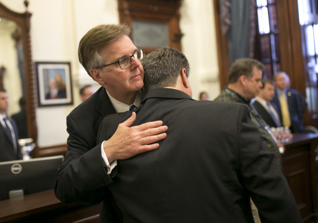 Lt. Gov. Dan Patrick, left, hugs Scot Rice during a discussion about guns in schools at the Governor's Reception Room at the Capitol in Austin, Texas,...