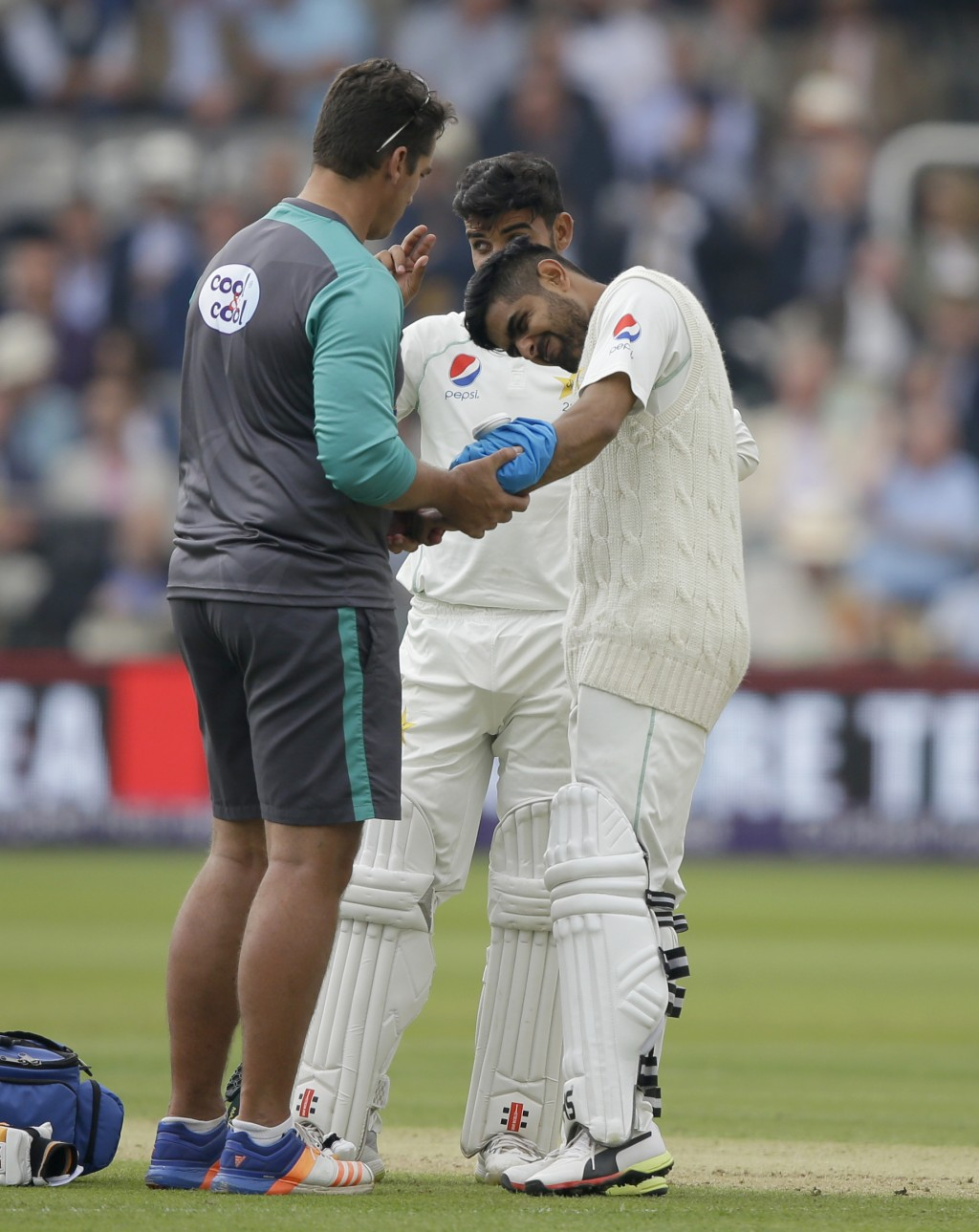 Pakistan's Babar Azam reacts as ice is applied to an injury caused by a ball bowled by England's Ben Stokes during the second day of play of the first...